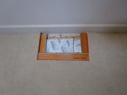 Bleach stained off white berber carpet along wall during patching carpet