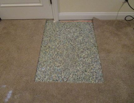 Stained light brown carpet near doorjamb during patching