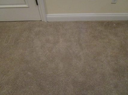 Stained light brown carpet near doorjamb after patching