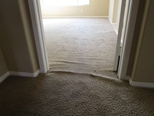 Loose and buckled brown sculptured carpet in doorway leading to bedroom before stretching carpet