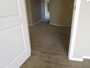 Loose and buckled brown sculptured carpet in doorway before stretching carpet