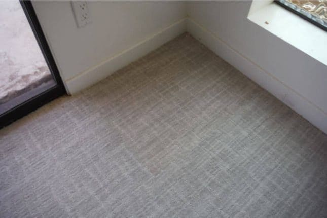 Bleach damaged gray patterned carpet after patching in corner of room