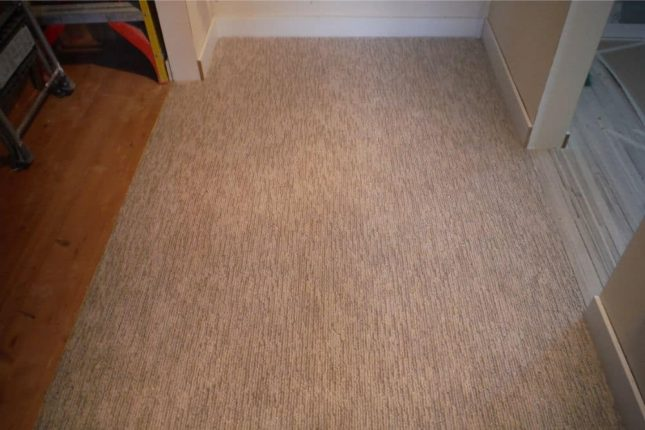 Gray berber carpet between closet and vanity after patching to fill voids