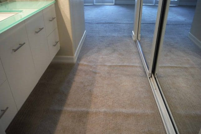 Gray berber loose and buckled carpet in vanity and into bedroom before stretching