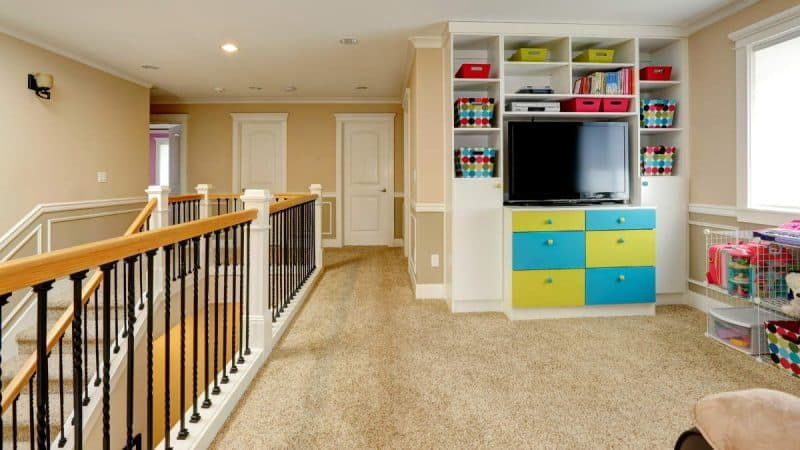 Upper level of modern house furnished with built-in cabinets, tv, storage units. View of staircase and railings